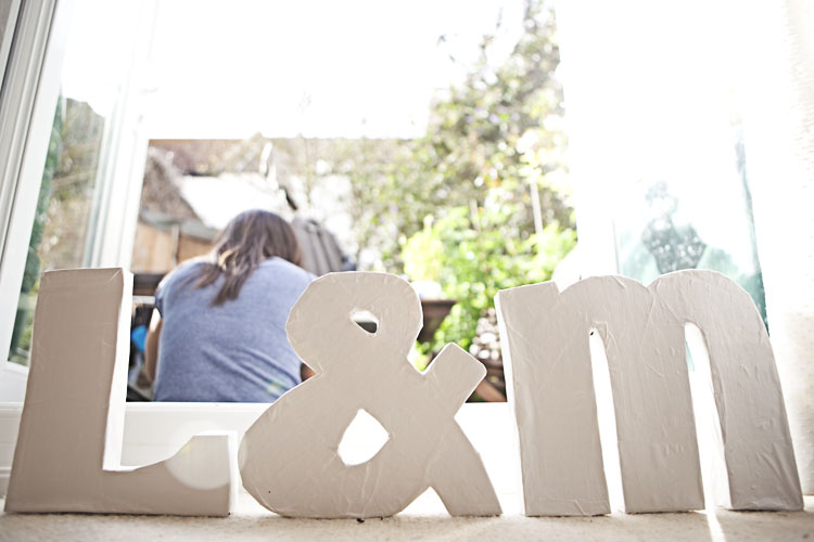 Monica behind the brightly lit cardboard typographic 3D letters